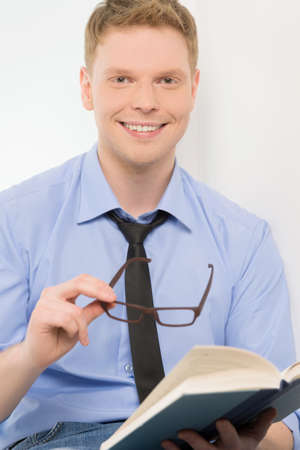 young man holding book and smiling. handsome guy with glasses on white background photo