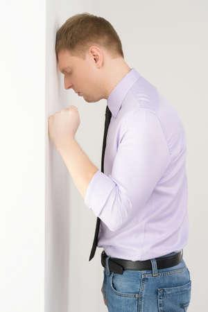anguished: Vista laterale di infelice uomo maturo. ragazzo appoggiato la testa contro il muro