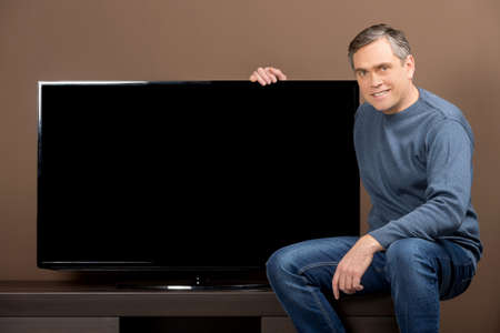 hd tv: older man sitting and holding tv set. guy with grey hair on brown background