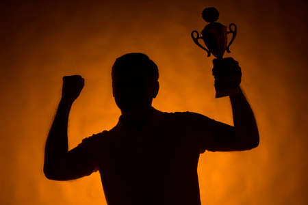 waist up: silhouette of man holding champion cup. waist up man standing on orange background