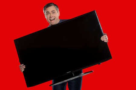 older man holding plasma screen. grey haired man standing on red background photo