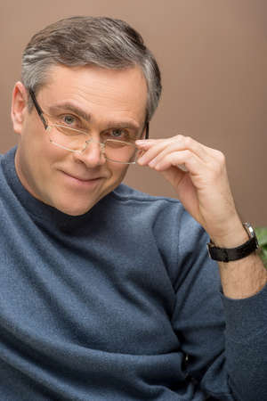 closeup of older man looking into camera. man wearing glasses and watches and smiling photo