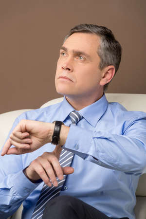looking at watch: closeup of older man looking at watch. portrait of businessman sitting at sofa and thinking