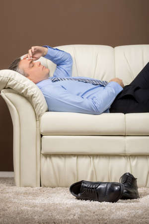 shoes off: older businessman lying on white sofa. man took off shoes and sleeping on couch Stock Photo