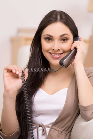 PHONE LINE: beautiful brunette talking on telephone and smiling. close up of young girl holding receiver and cord