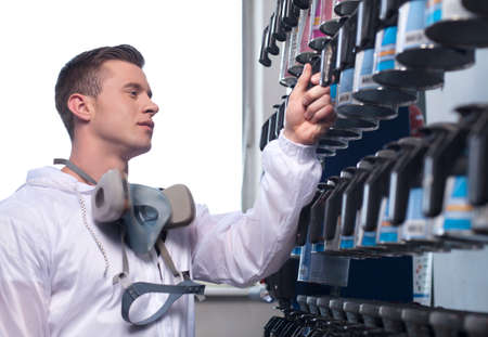 car shop: waist up of man selecting car paint. closeup of man wearing overall and working in shop Stock Photo
