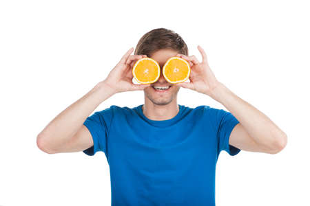 waist up: young man holding two oranges. waist up of guy wearing blue t-shirt