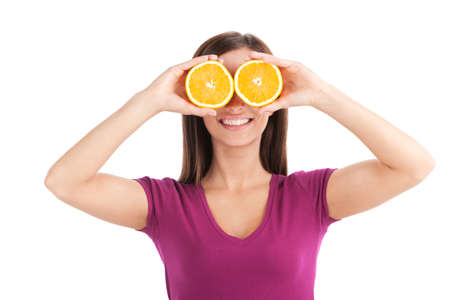 goofing: young girl holding two oranges. waist up of woman wearing pink t-shirt
