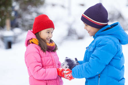 little boy helping small girl and smiling. children playing in park and making snowballs photo
