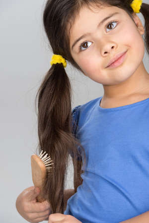nice little girl combing hair. school girl smiling and looking good photo