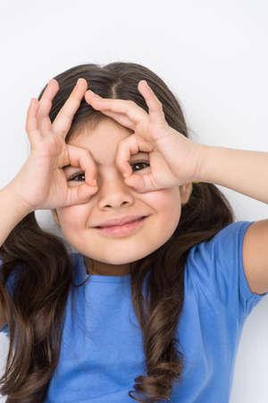 nettes kleines Mädchen gestikulierte und Spielen. Schule Mädchen macht Handferngläser