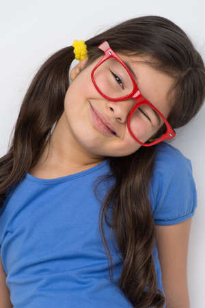 goofing: nice little girl wearing red glasses. cute girl playing and goofing around Stock Photo
