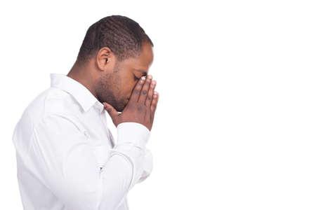 hombre orando: hombre negro de orar y de pie frente a la derecha. El hombre vestido con camisa blanca ojos cerrados Foto de archivo