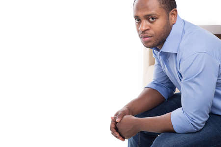 leaning forward: handsome black male in blue shirt. Attractive man on couch leaning forward  Stock Photo