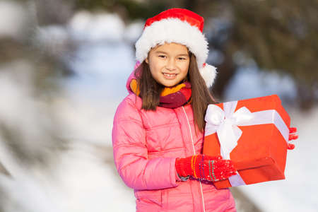 nice girl holding present outside. young girl standing outside on snow photo