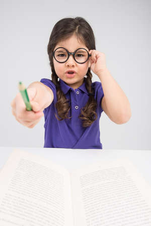 forcing: little girl pointing pencil and talking. serious facial expression of pretty child Stock Photo