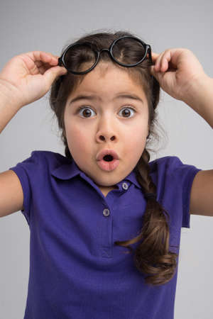 nice little girl holding glasses. pretty child removing glasses with surprise photo