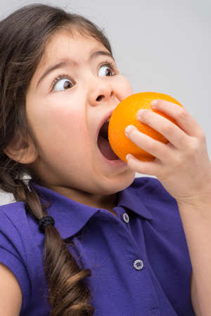big mouth: little girl biting big orange. pretty girl opened mouth and eating