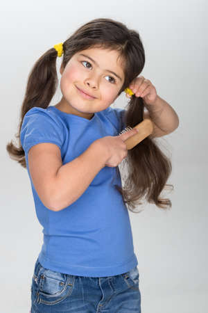 combing hair: little girl smiling and combing hair. pretty girl wearing jeans and blue t-shirt