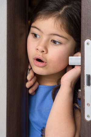 furtively: nice little girl opened door. pretty girl pushing door open Stock Photo