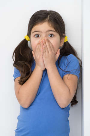 little girl surprised: little girl covering face and mouth. nice girl standing against wall