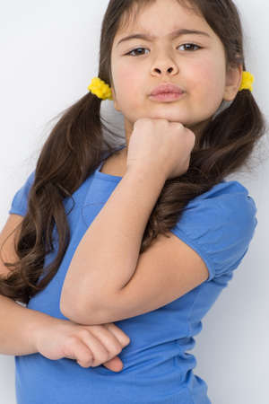 nice little girl pretending serious. pretty child standing against wall photo