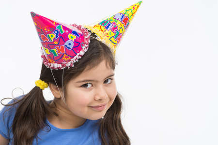 goofing: funny girl wearing birthday hat. school girl playing and goofing around Stock Photo