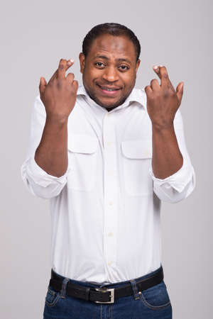 handsome black man crossed his fingers. man has anxious face expression  Stock Photo