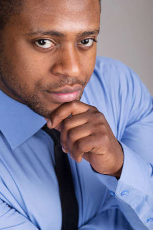 good looking black man thinking. handsome man folded hands and thinking photo