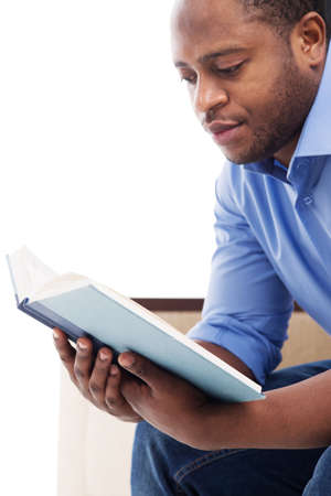 handsome black man reading book. Attractive male in blue shirt sitting on couch photo