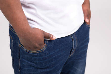 black man wearing blue jeans. man standing and keeping hands in pockets photo