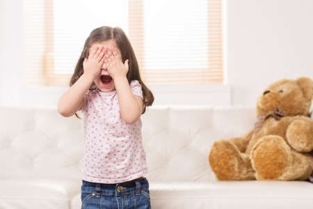 charming little girl covered eyes. nice girl playing hide and seek photo