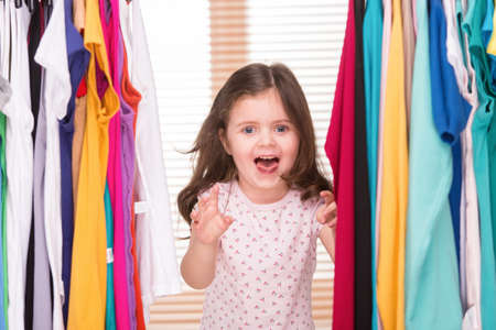 funny little girl playing with clothes. nice girl standing in wardrobe and smiling photo