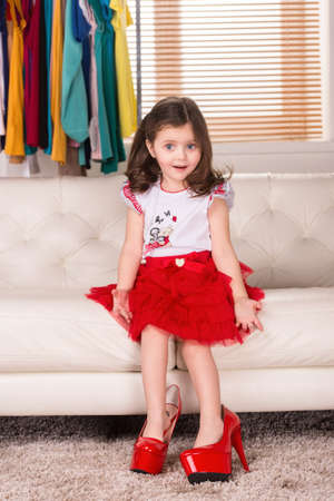 little girl wearing mom shoes. nice girl sitting on sofa and posing photo