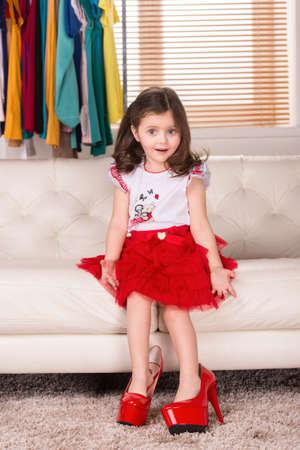 petite fille avec robe: petite fille qui porte des chaussures de maman. belle jeune fille assise sur le canapé et en posant