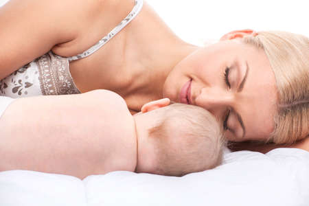 young mom lying in bed with baby. beautiful blond sleeping with little toddler photo