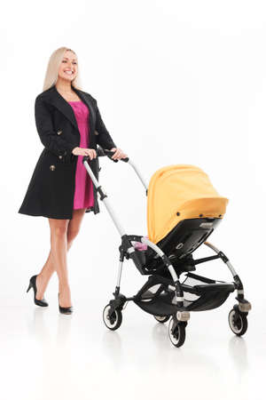 young beautiful mum with baby in stroller. beautiful blond strolling toddler and smiling photo