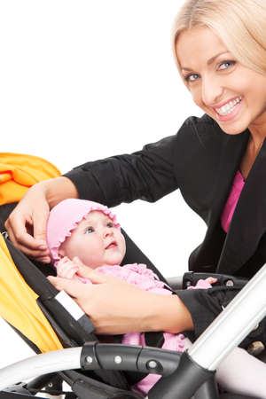 young beautiful mum with baby in stroller. beautiful blond hugging toddler and smiling photo