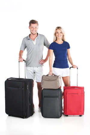 happy couple waiting departure with luggage. man and woman standing on white background photo