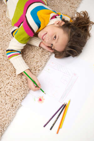 waistup: schoolgirl lying on carpet and drawing pictures. waist-up and top view of little girl smiling
