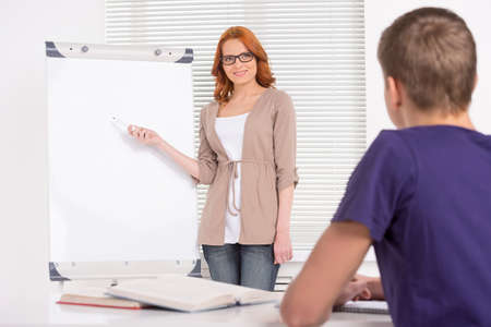 coursework: young attractive tutor girl teaching. young man sitting and listening to teacher