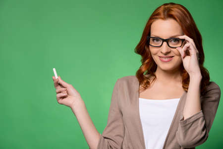 Beautiful business woman smiling over green background. confident happy smiling student holding chalk photo