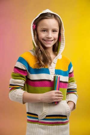 colegiala: cute little girl holding lápices. colegiala bonita de pie sobre fondo amarillo y la sonrisa Foto de archivo