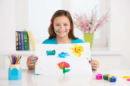 little girl showing picture and smiling. cute kid holding colorful picture