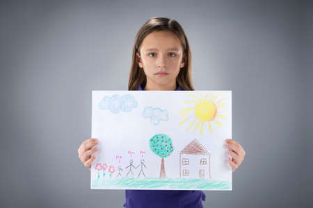 dissappointed: sad little girl holding picture. cute kid standing on grey background Stock Photo