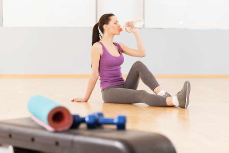 Pretty sporty young slim brunette. woman sitting on floor and drinking water photo