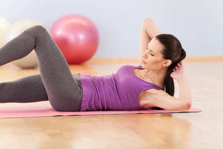 slim mid woman do her fitness exercises. pretty girl working out on floor and holding hands behind 写真素材