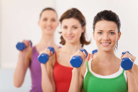 arm muscles: Aerobics class of diverse women of different ages. girls working out in gym with dumbbells flexing their arm muscles