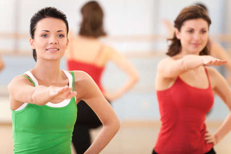 waist up: waist up portrait of instructor with fitness class. young girls performing step aerobics exercise in gym