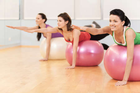 fit ball: women working out in gym doing pilates. group of young girls lying on balls